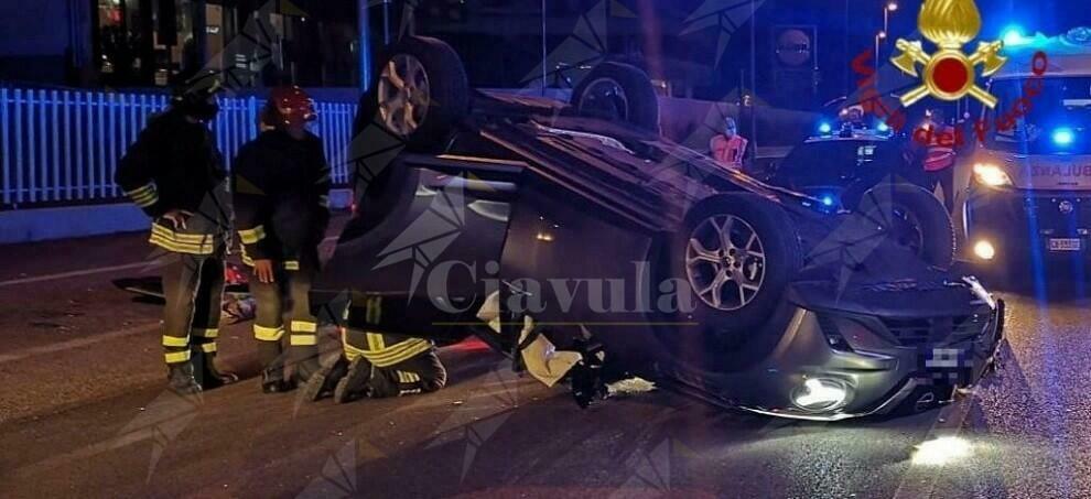 Con l'auto si schianta contro un veicolo in sosta e si ribalta